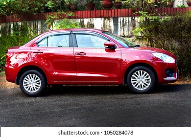 TRIVANDRUM, KERALA, INDIA, MARCH 18, 2018: A Gallant red AMT Maruti Suzuki Dzire 1.2 VVT Allure Edition car parked by the roadside in front of a house.