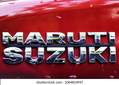 TRIVANDRUM, KERALA, INDIA, MARCH 29, 2018:  Shiny emblem of Maruti Suzuki car on a red car after the rains.