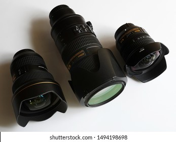 Trivandrum, Kerala, India, September 02, 2019: Top view of three Nikon lenses - 8-15 mm, 14-24 mm and 70-200 mm, f/2.8, on white background.