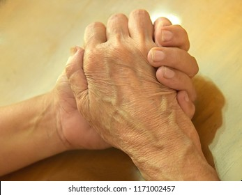 TRIVANDRUM, KERALA, INDIA, SEPTEMBER 03, 2018: Gesture of love and care. A daughter's protective hand. Woman holding the her mother's wrinkled hand, top-down composition. Mother's day. Women's day.