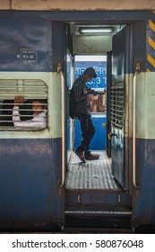 Trivandrum, Kerala, January 2 2017; Young man watching the screen of his smart phone while standing on the balcony on an Indian Railways train.