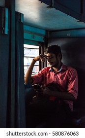 Trivandrum, Kerala, January 2 2017; Young man watching the screen of his smart phone while seated in a window seat on an Indian Railways train.