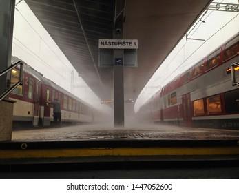 Trnava, Slovakia - 6/16/2017: Trainstation platform with parked trains during storm and raining in Trnava, Slovakia.