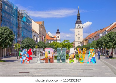 TRNAVA, SLOVAKIA - JULY 3, 2018: Pedestrian precinct with original hashtag art. Summer day. Trnava's pedestrian zone with renaissance Town tower - Trnava's silhouette and Church of the Holy Trinity.