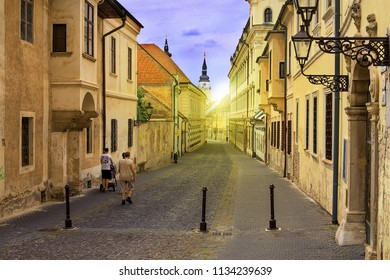 TRNAVA, SLOVAKIA - JULY 3, 2018: Old town street M. S. Trnavskeho with Town Tower in the background. Old houses of Trnava. Historical center of Trnava. Ancient street in old city. Golden hour with sun