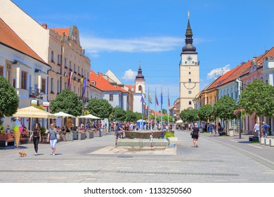 TRNAVA, SLOVAKIA - JUNE 3, 2018: Pedestrian zone (Hlavná street). In the background are renaissance Town tower - Trnava's silhouette and Church of the Holy Trinity (Jesuit Church). Trnava region.