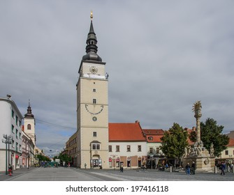 TRNAVA, SLOVAKIA - SEPTEMBER 24, 2013: Local and visitor stroll the Trojicne square, near the city tower, In Trnava, Slovakia