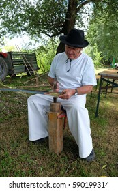 TRNOVEC, CROATIA - JULY 09, 2016: Farmer with hammer and iron tool on the tree stump is sharpening his scythe in Trnovec, Croatia on July 09, 2016.
