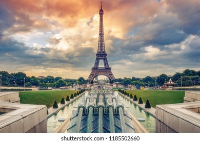 Trocadero Fountains and the Eiffel tower on a summer day with dramatic sunrise sky. Colourful travel background.