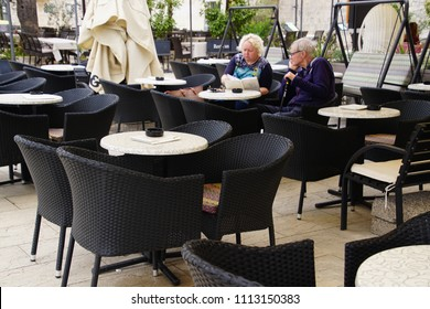 TROGIR, CROATIA - APR 15, 2018 -Senior couple in a coffee shop cafE on the waterfront of Trogir, Croatia