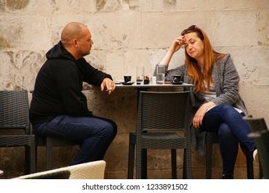 TROGIR, CROATIA - APR 15, 2018 - Couple in a coffee shop cafE on the waterfront of Trogir, Croatia