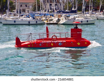 TROGIR, CROATIA - AUGUST 16, 2014. Red semi submarine crosses Trogir harbor. On the bottom of this funny touristic boat a set of transparent windows allow to explore the underwater world