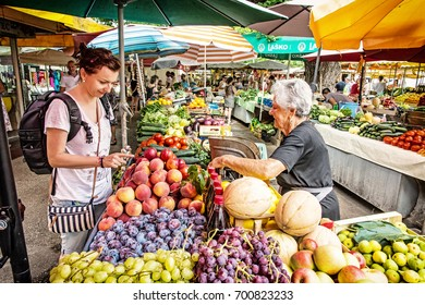 TROGIR, CROATIA - JULY 24, 2017: Young tourist woman buying fresh fruit from old woman at market hall, old town Trogir, Croatia. Travel destination.