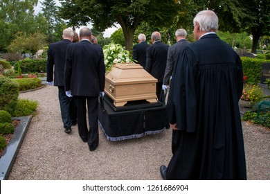 Troisdorf, Germany - July 22, 2011: six pallbearers dressed in black and a Lutheran pastor escorting a coffin across a cemetery to the grave