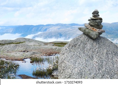 Troll (stone tower) placed on a big rock  marking the Kjerag hiking trail. Small lake with white flowers and a deep valley of the Lyssefjord in the background. Picture from Rogaland, Norway.