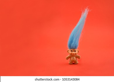 Troll toy stock images. Elf on a red background. Troll with blue hair