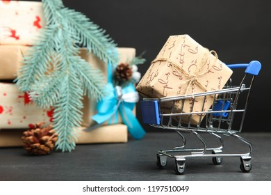 Trolley with Christmas gifts on black background. Concept New Year.