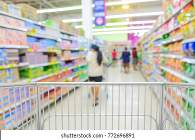 Trolley Kart Shopping in Supermarket or Hypermarket store with Blur Background of People in Dairy Product Section.