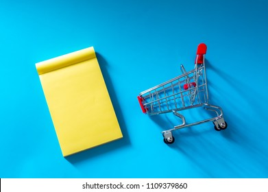 Trolley and notes isolated on blue background. Copy space and top view.
