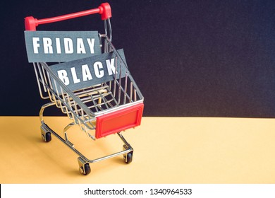 """A trolley on a black background with labels containing the inscription """"Black Friday"""". Toned. Copy space."""
