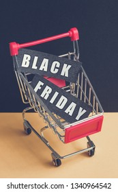 """A trolley on a black background with labels containing the inscription """"Black Friday"""". Toned. Vertical"""