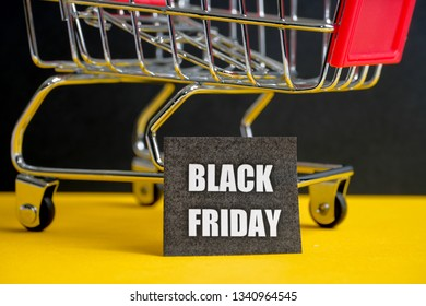 """A trolley on a black background with labels containing the inscription """"Black Friday""""."""
