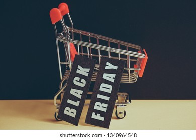 """A trolley on a black background with labels containing the inscription """"Black Friday"""". Toned."""