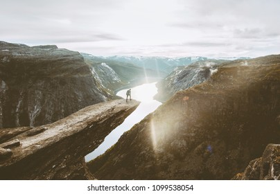 Trolltunga cliff and man traveler standing on edge in Norway adventure travel extreme lifestyle active vacations outdoor sunset mountains and lake