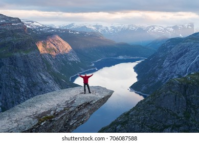 Trolltunga is a tourist attraction of Norway. Awesome beautiful place. Tourist is standing on a rock. Evening landscape in the mountains. Beautiful sunset