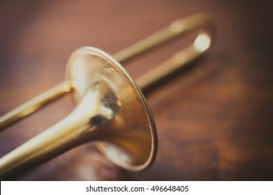Trombone bell on brown wooden parquet, bell detail selective focus