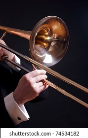 A trombone is held by the hands of a man in a tuxedo, isolated on black.
