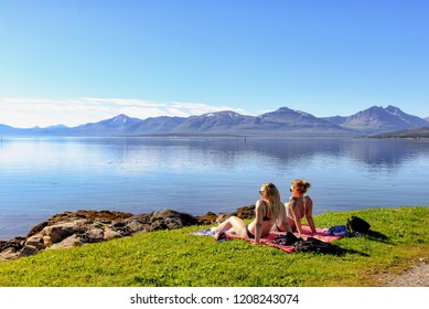 Tromso, Norway - August 18, 2016: Two unidentified girls sunbathing in Tromso southern beach. Tromso is the largest urban area in Northern Norway and the third largest north of the Arctic Circle