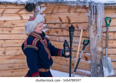 Tromso, Norway -  December 2018 : Man dressed in traditional Sami costume holding bottle with flammable fire starting liquid about to start fire in winter, Tromso region