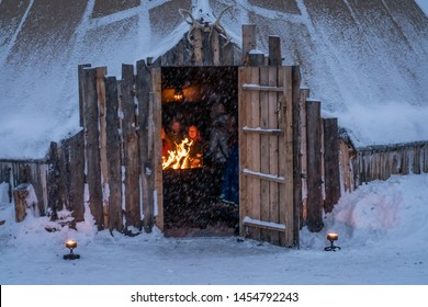 Tromso, Norway -  December 2018 : Tourists gathering by the fire inside a large Sami tent to listen to traditional folk stories in winter, Tromso region