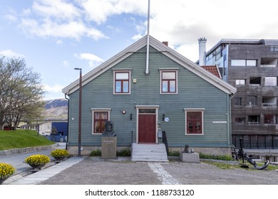 Tromso, Norway - June 1, 2018: Exterior view of the Polar Museum with a Roald Amundsen statue