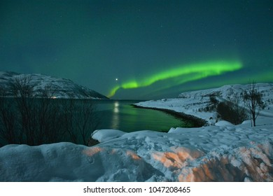 TROMSO, NORWAY - MARCH 6, 2017: The northern lights (Aurora Borealis) over Seljelvnes, Troms by the sea and the snowy mountains