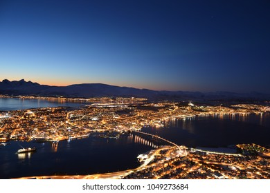 TROMSO, NORWAY - MARCH 6, 2017: The northern lights (Aurora Borealis) and the city scape from Fjellheisen Peak over the city