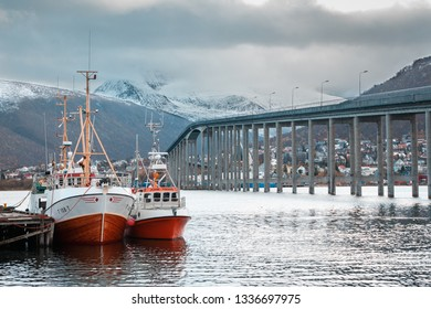 Tromso, Norway - November 10, 2018: General view of the port of Tromso, with two boats in the foreground, the Tromso bridge and the snowy mountains in the background.