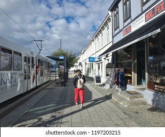 Trondheim, Norway - 18 of September, 2018: a girl in the red pants at the streets of the city downtown. Trondheim Tram.