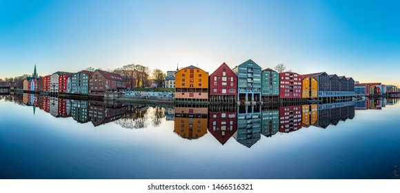 TRONDHEIM, NORWAY, APRIL 15, 2019: Colorful timber houses surrounding river Nidelva in the Brygge district of Trondheim, Norway