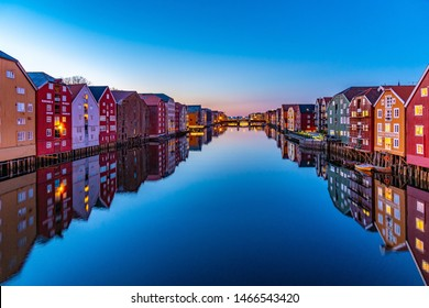 TRONDHEIM, NORWAY, APRIL 15, 2019: Sunset view of colorful timber houses surrounding river Nidelva in the Brygge district of Trondheim, Norway