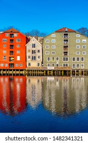 TRONDHEIM, NORWAY, APRIL 16, 2019: Colorful timber houses surrounding river Nidelva in the Brygge district of Trondheim, Norway