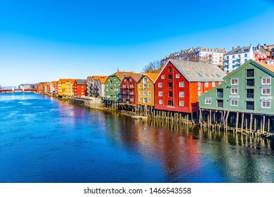 TRONDHEIM, NORWAY, APRIL 17, 2019: Colorful timber houses surrounding river Nidelva in the Brygge district of Trondheim, Norway