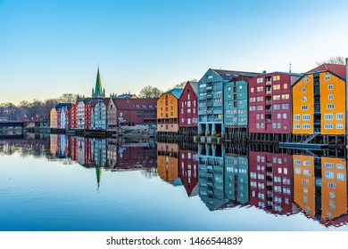 TRONDHEIM, NORWAY, APRIL 17, 2019: Sunset view of Nidaros cathedral and colorful timber houses surrounding river Nidelva in the Brygge district of Trondheim, Norway