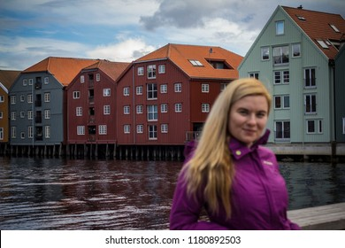Trondheim, Norway - August, 2018: Local girl in Trondheim city with the  colorful houses at the background