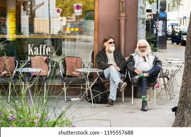 Trondheim, Norway - August 29th, 2018: Two local men with grey hair sitting outside a coffee shop in Trondheim, one of them wearing two eyeglasses at the same time.
