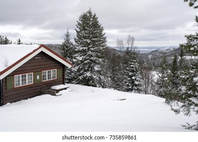 TRONDHEIM, NORWAY - MARCH 19, 2007. 'Elgsethitta' A hut in Bymarken, an area of hills and forests. Winter landscape with wooden cabin, trees heavy with snow and the Trondheim fjord in the background.