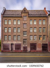 TRONDHEIM, NORWAY - SEPTEMBER 07, 2019: The front facade of a derelict brick building that has obviously seen better days.