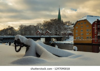 Trondheim, Sor-Trondelag / Norway - 01 23 2019:ld houses and magazines by Nidelva river in Trondheim, Nidarosdomen Cathedral in back. Beautiful winter time in Norway.