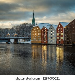 Trondheim, Sor-Trondelag / Norway - 01 23 2019:Old wooden buildings, magazines, by the shores of Nidelva river, winter time in Trondheim, Norway.